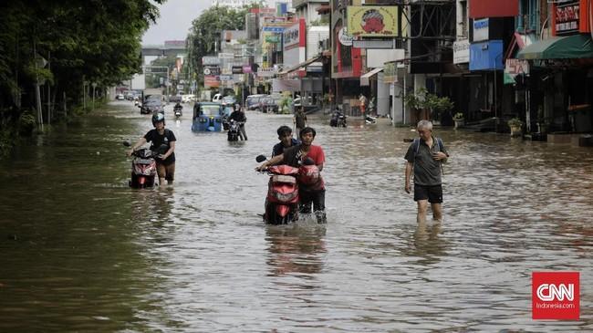Warga mendorong motor yang dimatikan saat melintasi jalan protokol kawasan Kelapa Gading, Jakarta Utara yang tergenang banjir, 1 Januari 2020. (CNN Indonesia/Adhi Wicaksono)