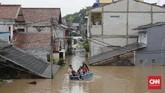 Menggunakan perahu darurat, warga melintasibanjir yang merendam daerah permukiman di Cipinang Melayu, Jakarta, Rabu (1/1/2020). (CNN Indonesia/Adhi Wicaksono)