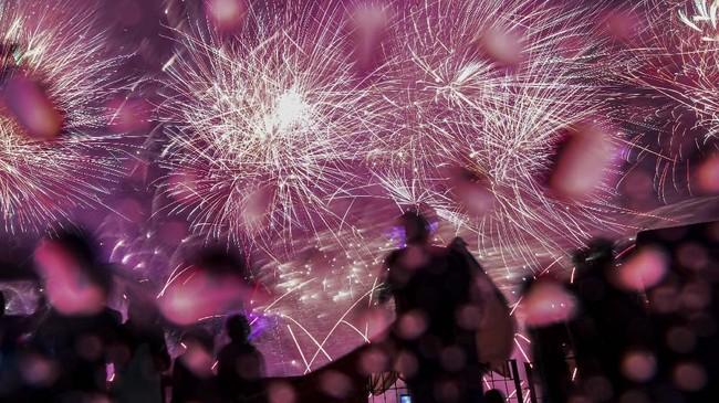 Sejumlah warga masyarakat menikmati pesta kembang api di Pantai Lagoon, Taman Impian Jaya Ancol. Pesta kemang api tersebut untuk menyambut tahun baru 2020. (ANTARA FOTO/Muhammad Adimaja).