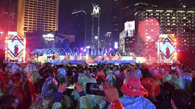 Sejumlah warga mengenakan jas hujan dan menggunakan payung saat menikmati hiburan dalam acara hari bebas kendaraan bermotor (HBKB) atau 'car free night' di kawasan Bundaran Hotel Indonesia. (ANTARA FOTO/Aditya Pradana Putra).