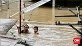 Di kawasan pemukiman padat penduduk Pendagegan Timur IV masih ada rumah warga yang terendam air setinggi tiga meter, Jakarta, Kamis (2/1). Warga hanya dapat pasrah untuk menunggu air surut. (CNN Indonesia/Andry Novelino)