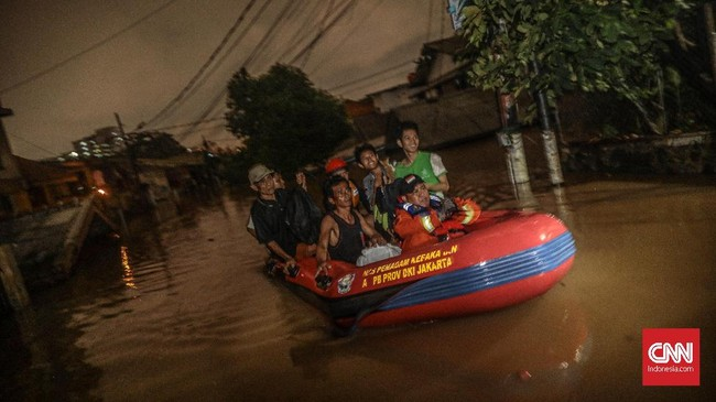 Hingga malam hari petugas masih melakukan evakuasi terhadap warga yang terjebak di rumah mereka. Banyak dari mereka terjebak di rumah dengan bayi, balita, atau lansia sehinggamembutuhkan pertolongan cepat. (CNN Indonesia/Bisma Septalisma)