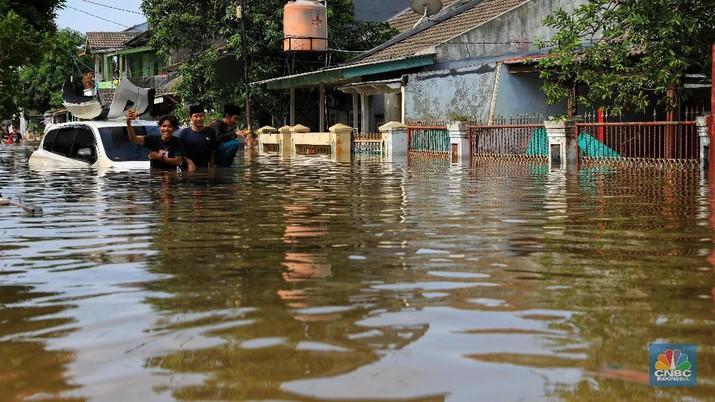 Warga memfoto mobil yang hanyut akibat banjir di Kawasan Ciledug Indah, Tangerang, Kamis (2/1/2020).
