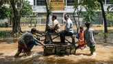 Dua orang warga menaiki gerobak yang didorong sejumlah anak saat melintasi genangan banjir di kawasan Jalan Bungur Besar Raya, Jakarta, Kamis (2/1). (ANTARA FOTO/M Risyal Hidayat)