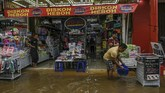 Pekerja membuang air yang masuk ke dalam toko saat banjir menggenangi kawasan Pasar Baru di Jakarta, Kamis (2/1/2020). (ANTARA FOTO/Nova Wahyudi)