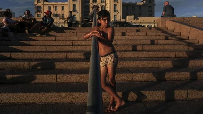 Seorang anak laki-laki berdiri di tangga di pantai Ramirez, saat matahari terbenam di Montevideo pada Sabtu (28/12).(Photo by Eitan ABRAMOVICH / AFP)