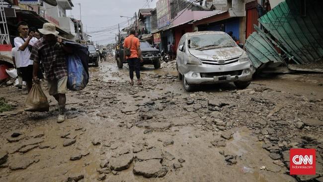 Lumpur menempel di kendaraan yang rusak dan bergelimpangan di sepanjang jalan. Sejumlah mobil dan bus ikut terbalik. (CNN Indonesia/Adhi Wicaksono)