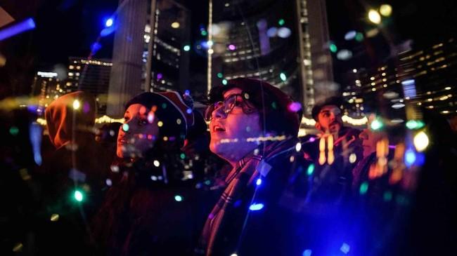 Salma dan Sabrina Wennekers menonton perayaan Tahun Baru sebelum tengah malam di Nathan Philips Square di Toronto, Selasa, (31/12). (Christopher Katsarov/The Canadian Press via AP)