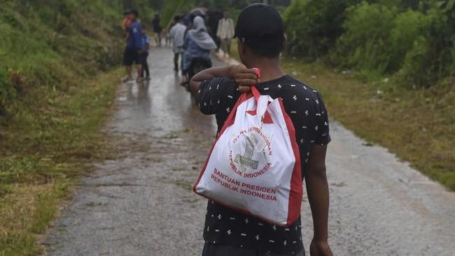 Warga korban longsor membawa bantuan dari Presiden Joko Widodo di Sukajaya, Bogor, Jawa Barat, Minggu (5/1/2020). (ANTARA FOTO/Akbar Nugroho Gumay)