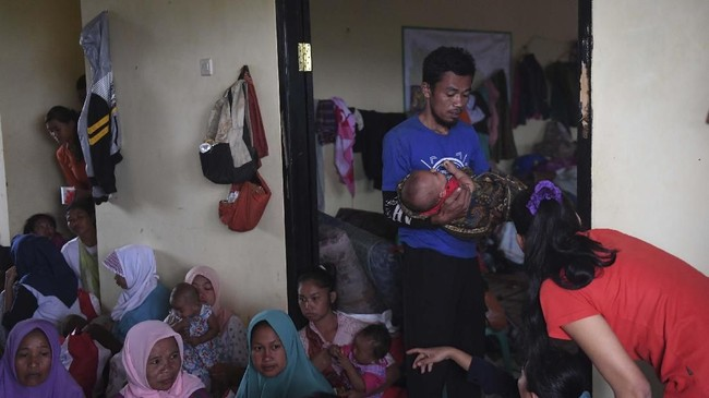 Warga korban longsor menggendong bayinya saat beristirahat di posko penampungan di Sukajaya, Bogor, Jawa Barat, Minggu (5/1/2020). Presiden Jokowi membagikan 6.000 paket bantuan untuk para pengungsi. (ANTARA FOTO/Akbar Nugroho Gumay)
