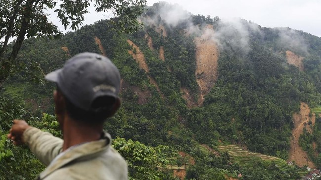 Seorang pria memerhatikan Gunung Kembang yang longsor di Sukajaya, Bogor, Jawa Barat, Minggu (5/1/2020). Ribuan warga Sukajaya terisolasi akibat longsor dan banjir bandang yang memutus akses sehingga mempersulit pengiriman bantuan dan proses evakuasi. (ANTARA FOTO/Akbar Nugroho Gumay)