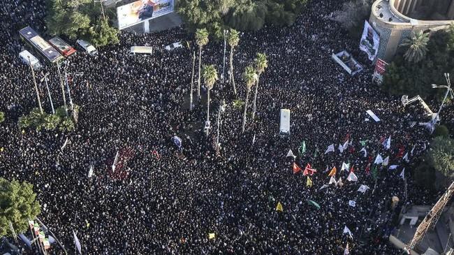 Sebagian besar warga mengenakan setelan hitam sambil membawa bendera Iran dan foto Soleimani, beberapa membawa poster bernada anti-Amerika.(Morteza Jaberian/Mehr News Agency via AP)