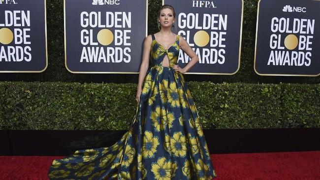 Taylor Swift tampil manis dengan gaun berbahan sutra rancangan Etro. Rona biru gaun dipercantik dengan motif bunga-bunga berwarna kuning. (Photo by Jordan Strauss/Invision/AP)