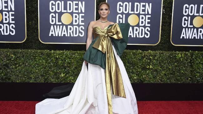 Suasana Natal mungkin masih dirasakan Jennifer Lopez alias JLo. Gaun Valentino yang ia kenakan lebih mirip pembungkus kado Natal dengan aksen pita super besar. (Photo by Jordan Strauss/Invision/AP)