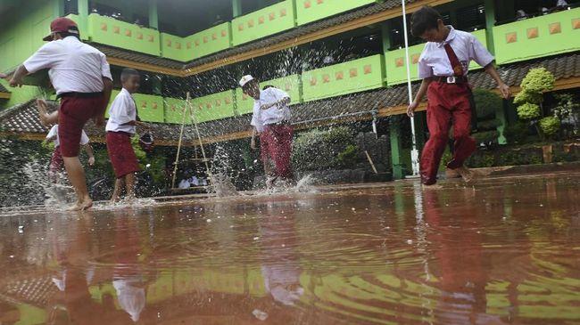 FOTO: Tak Gentar Hadapi Banjir di Hari Pertama Sekolah
