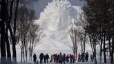 Turis berjalan di depan patung es menjelang pembukaan Festival Es dan Salju di Harbin, Heilongjiang, China, pada 4 Januari 2020. (NOEL CELIS / AFP)