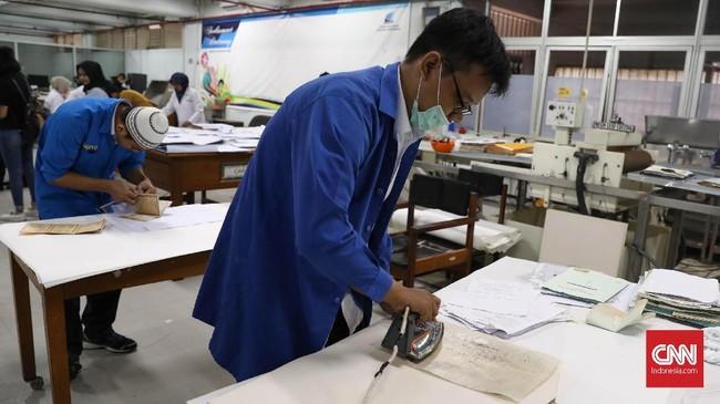 Menggunakan wax paper (kertas yang berbahan lilin) yang berfungsi melapisi tulisan agar tidak lengket saat pengeringan menggunakan setrika. (CNNIndonesia/Safir Makki)
