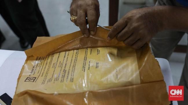 Petugas sangat hati-hati membuka dokumen dari warga yang kondisi masih basah. Membuka perlahan agar tidak sobek menggunkan pinset. (CNNIndonesia/Safir Makki)