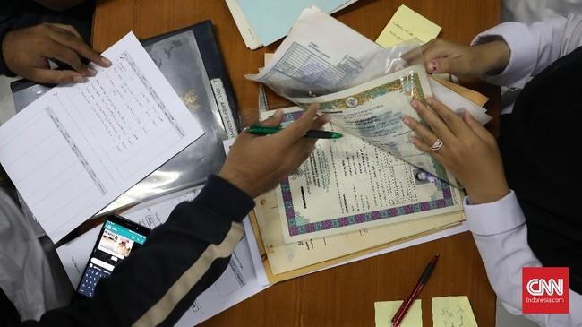 Arsip Nasional RI (ANRI) menawarkan layanan restorasi atau perawatan segala bentuk dokumen pribadi atau keluarga yang terdampak bencana banjir di Jakarta, Bogor, Depok, Tangerang, dan Bekasi (Jabodetabek)pada awal 2020. (CNNIndonesia/Safir Makki)