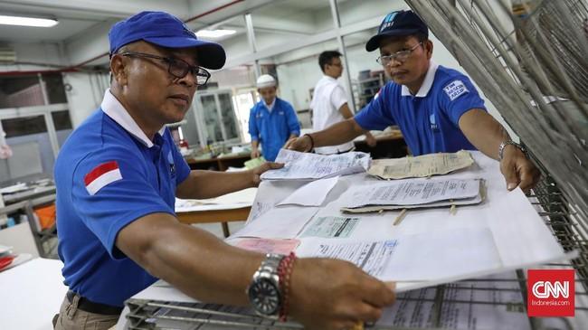 Petugas mengangin-anginkan sejumah dokumen yang berhasil dipilah di tempat penjemuran. (CNNIndonesia/Safir Makki)