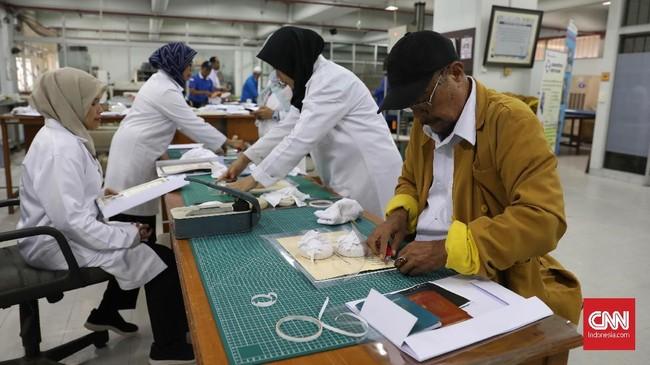Setelah proses pengeringan, semua dokumen dilaminasi atau enkapsulasi untuk melindungi fisik dari dokumen. (CNNIndonesia/Safir Makki)