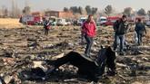 Petugas baru mendekat ke lokasi kejadian setelah koraban api akibat pesawat jatuh itu padam. (Photo by - / AFP)