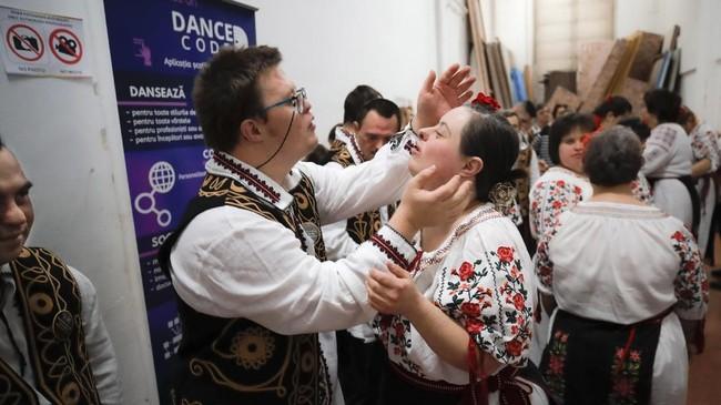 Dua orang anak dengan down syndrome (ADS) terlihat berpelukan sebelum pementasan di Bucharest, Romania, pada awal Desember lalu. (AP Photo/Vadim Ghirda)