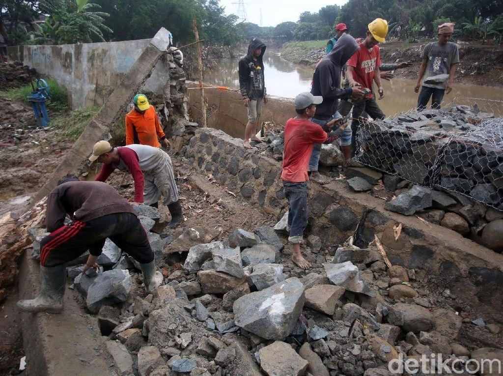 Sejumlah pekerja bahu membahu memperbaiki tanggul Kali Bekasi yang jebol di kawasan Perumahan Pondok Mitra Lestari, Bekasi, Jawa Barat, Kamis (9/1/2020).