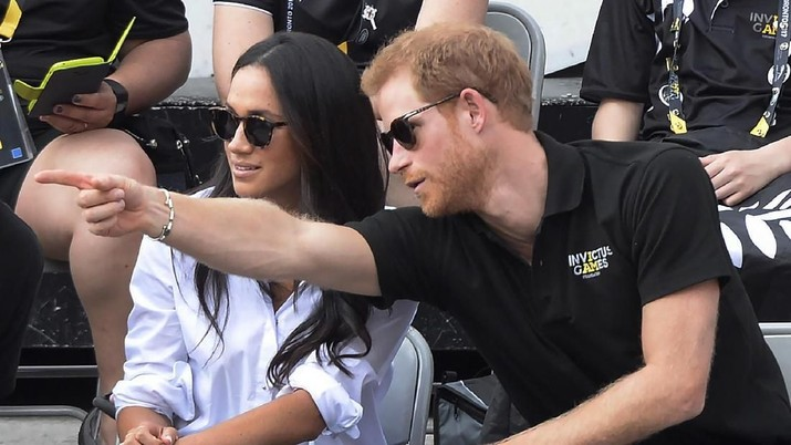 FILE - In this Monday, Sept. 25, 2017 file photo Prince Harry and his then girlfriend Meghan Markle attend a wheelchair tennis event at the Invictus Games in Toronto. In a stunning declaration, Britain's Prince Harry and his wife, Meghan, said they are planning