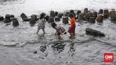 Anak-anak bermain di pinggir laut saat gelombang air laut yang tinggi di kawasan Muara Baru, Jakarta, Kamis, 9 Januari 2020. (CNNIndonesia/Safir Makki)