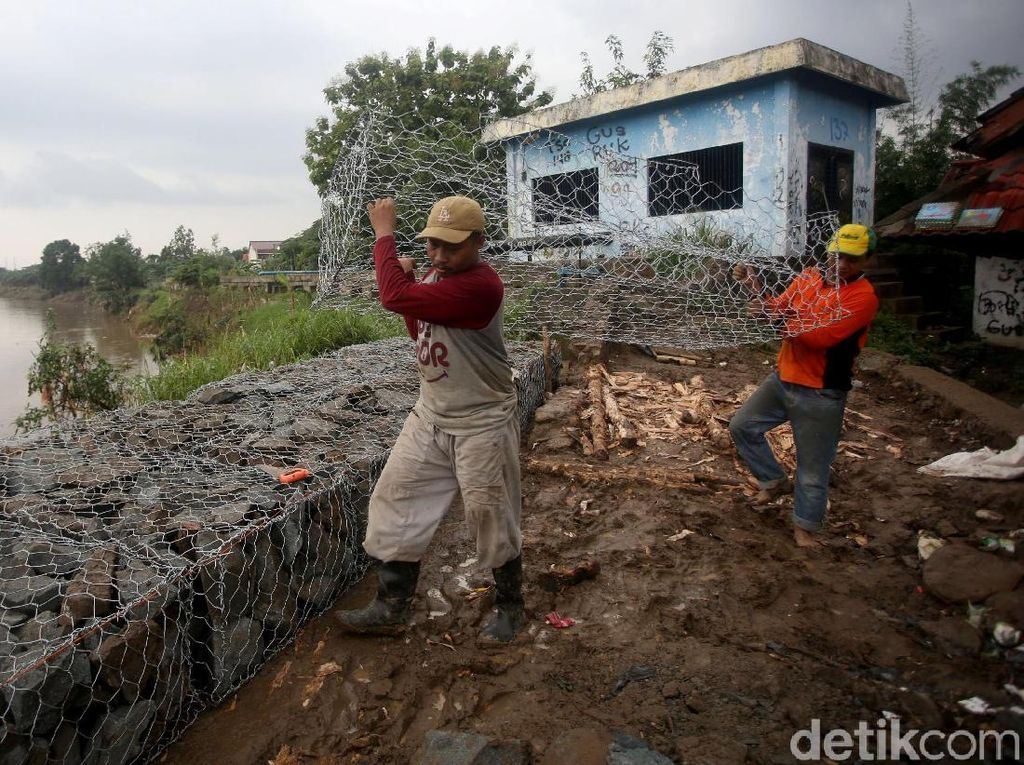 Para pekerja melakukan pengerjaan batu bronjong untuk perbaikan sementara tanggul sungai Bekasi yang sebelumnya jebol hingga menyebabkan rumah warga terendam banjir.