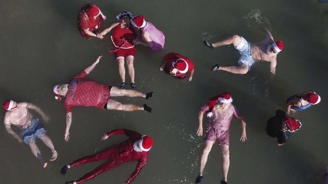 Anggota kelompok Santa Klaus terlatih yang berasal dari negara-negara Eropa dan Amerika Serikat berenang terapung dekat Laut Mati di Jericho, Israel. (AP Photo/Ariel Schalit)