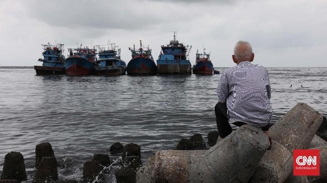 Warga menatap ke laut lepas, sementara kapal melempar sauh saat terjadi gelombang air laut tinggi di kawasan Muara Baru, Jakarta, Kamis, 9 Januari 2020. (CNNIndonesia/Safir Makki)