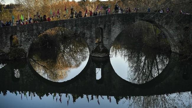 Tiga Raja yang menunggang kuda melambaikan tangan pada orang-orang yang melintas jembatan Magdalena di sungai Arga, di Pamplona, Spanyol bagian utara. (AP Photo/Alvaro Barrientos)