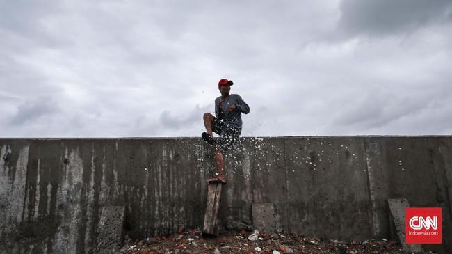 Warga melihat gelombang air laut yang tinggi di kawasan Muara Baru, Jakarta, 9 Januari 2020. Badan Meteorologi, Klimatologi, dan Geofisika (BMKG) memperkirakan daerah pesisir Jakarta Utara mengalami air pasang maksimum pada 9 Januari hingga 11 Januari 2020. (CNNIndonesia/Safir Makki)