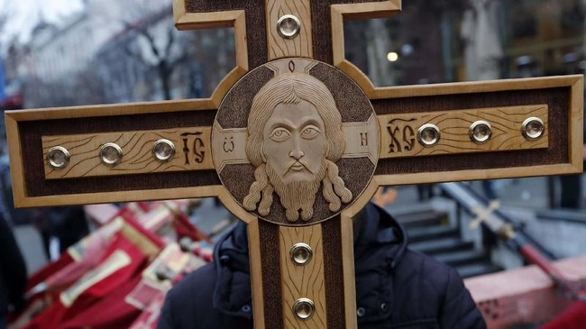 Seorang pria memegang salib pada suatu aksi di Belgrade, Serbia, untuk memprotes pengekangan kebebasan beragama di negara-negara tetangga Serbia. (AP Photo/Darko Vojinovic)