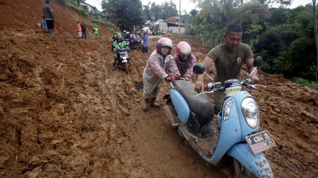 Sebanyak 11 desa di Kecamatan Sukajaya sempat terisolir akibat banjir bandang dan tanah longsor. Tampak warga melewati tebalnya lumpur dan tanah yang menutupi jalan. (ANTARA FOTO/Yulius Satria Wijaya/pd.)