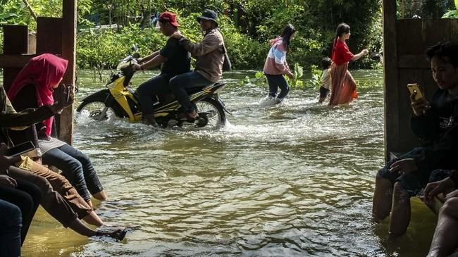 Karena banjir, jalan sempat terputus. Warga menembus jalan desa yang terendam banjir akibat jebolnya tanggul Sungai Tuntang di Desa Tlogorejo, Guntur, Kabupaten Demak, Jawa Tengah, Minggu (12/1/2020). ANTARA FOTO/Aji Styawan