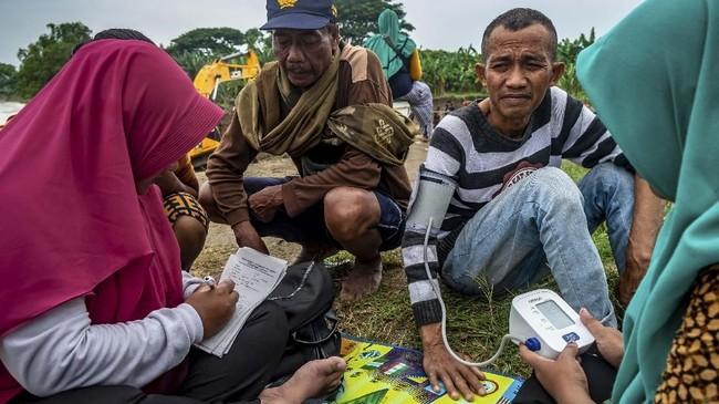 Petugas memeriksa kesehatan korban banjir Sungai Tuntang yang jebol di atas tanggul Desa Trimulyo, Guntur, Kabupaten Demak, Jawa Tengah, Sabtu (11/1/2020). ANTARA FOTO/Aji Styawan