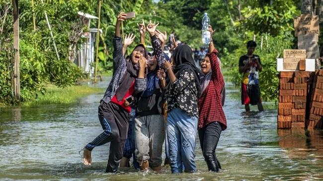 Sejumlah remaja berswafoto di jalan desa yang terendam banjir akibat jebolnya tanggul Sungai Tuntang di Desa Tlogorejo, Guntur, Kabupaten Demak, Jawa Tengah, Minggu (12/1/2020). ANTARA FOTO/Aji Styawan