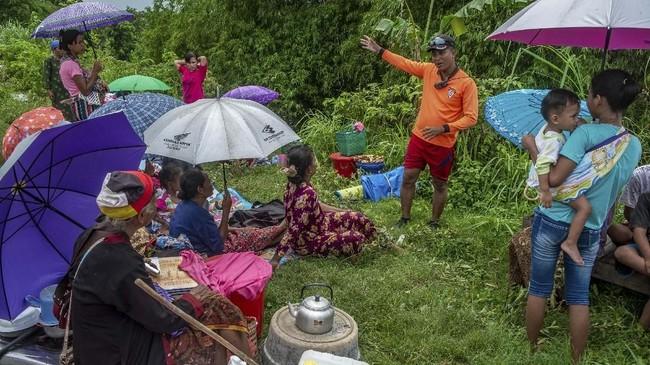 Petugas BPBD (kedua kanan) membujuk sejumlah warga yang mengungsi di atas tanggul untuk dievakuasi dari lokasi banjir di Desa Trimulyo, Guntur, Kabupaten Demak, Jawa Tengah, Kamis (9/1/2020). ANTARA FOTO/Aji Styawan