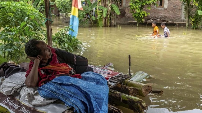 Warga bertahan di depan rumahnya yang terendam banjir akibat Sungai Tuntang jebol di Desa Trimulyo, Guntur, Kabupaten Demak, Jawa Tengah, Jumat (10/1/2020). ANTARA FOTO/Aji Styawan