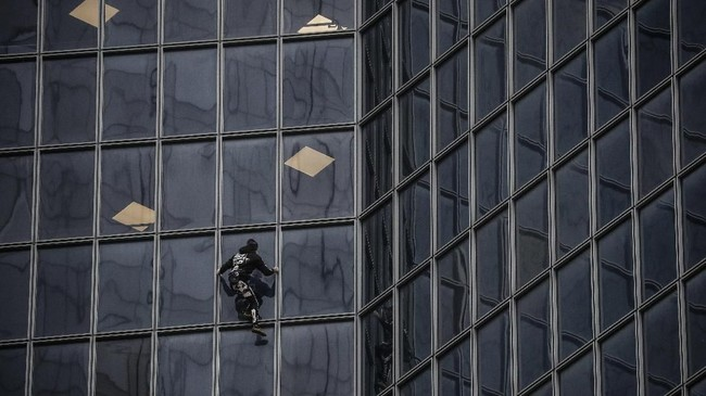 Robert menyelesaikan aksinya setelah 52 menit memanjat. (Photo by Thomas SAMSON / AFP)