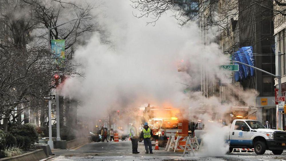 Uap mengepul dari jalan saat sejumlah kendaraan terpaksa berhenti karena banjir di jalan di Upper West Side Manhattan. (AP Photo/Richard Drew)
