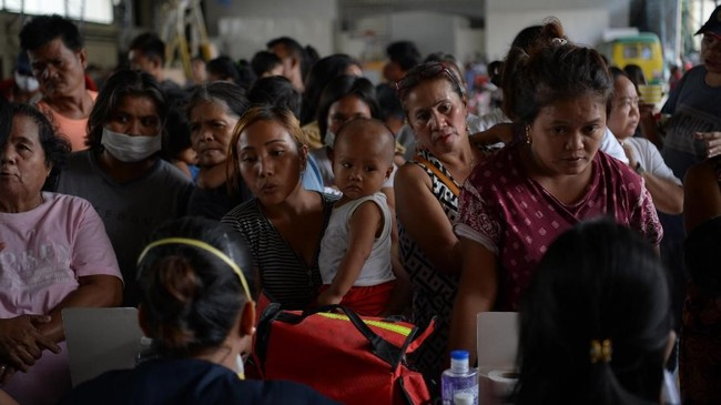 Evacuees from towns affected by the eruption of Taal volcano queue up to have their children checked by medical personnel at an evacuation center in Tanauan town, Batangas province south of Manila on January 14, 2020. (Photo by Ted ALJIBE / AFP)