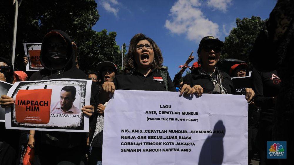 Demonstran berdatangan ke Balai Kota Jakarta dengan membawa poster yang bertuliskan Anies untuk turun dari jabatannya sebagai gubernur. (CNBC Indonesia/Andrean Kristianto)