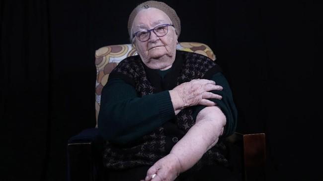 Helena Hirschjuga memiliki tato penghuni kamp Auschwitzbernomor A 20982. (Photo by MENAHEM KAHANA / AFP)