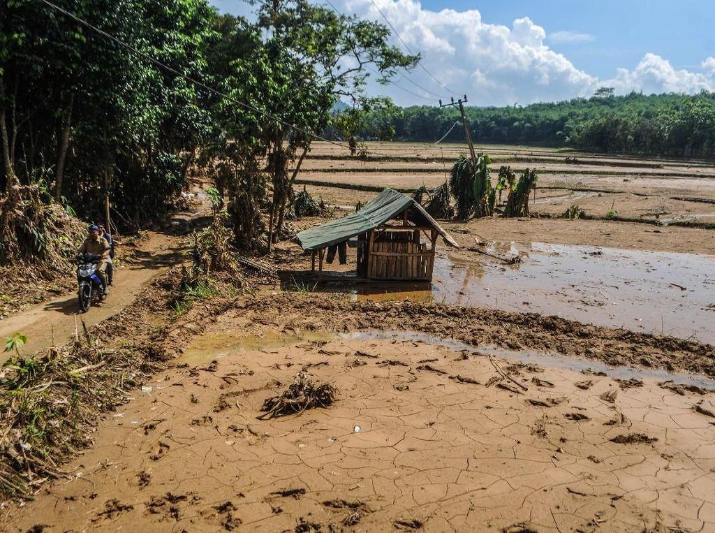 Warga melintas di areal persawahan yang rusak diterjang banjir bandang di Kampung Cimenteng, Lebak, Banten, Selasa (14/1/2020).