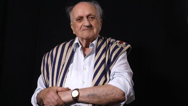 Pasukan Nazi membunuh sekitar 6 juta Yahudi saat PD II. Dov Landau (91) adalah salah satu dari sekian orang yang selamat. Dia masih menyimpan baju tahanan dan tidak menghapus tatobernomor 161400. (Photo by MENAHEM KAHANA / AFP)