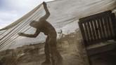 Seorang pria Palestina memeriksa kerusakan di kafenya setelah hujan deras menggutur Gada di pertengahan Januari. (AFP/Mohammed Abed)